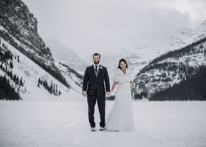 Full length of friends standing on snow covered landscape