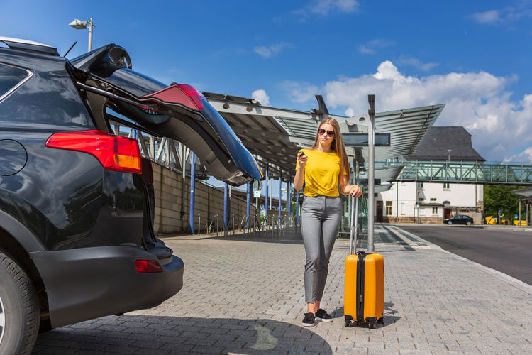 Full length of teenage girl with luggage closing car trunk while standing on street against sky
