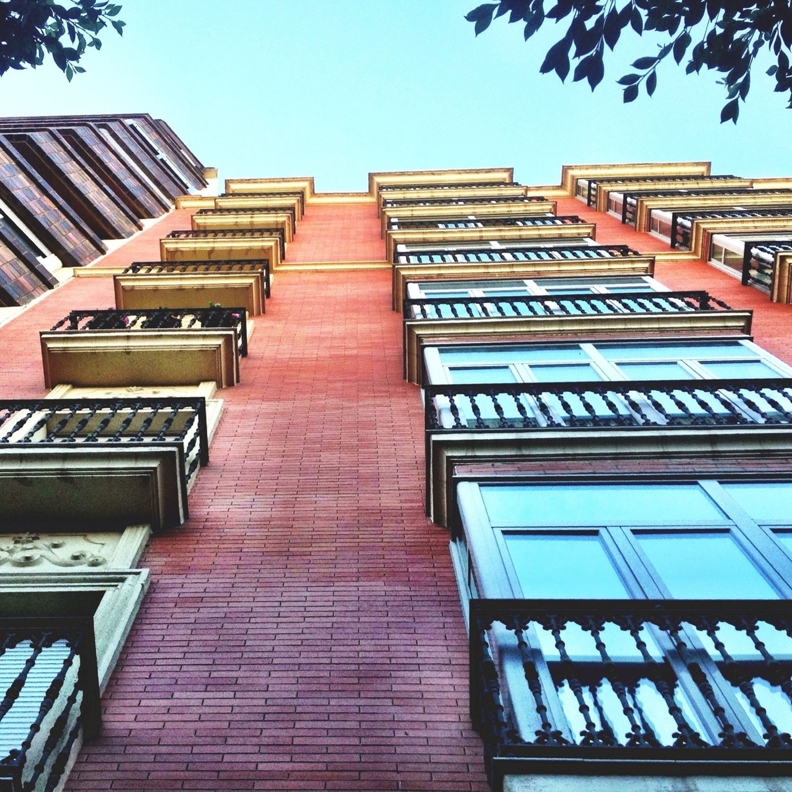 architecture, building exterior, built structure, low angle view, window, building, clear sky, city, residential building, residential structure, blue, day, sky, apartment, outdoors, no people, modern, office building, tall - high, sunlight