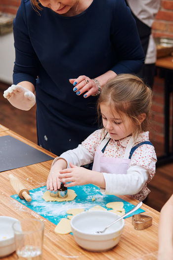 Midsection of woman assisting girl preparing cookie