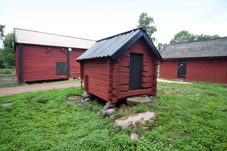 Barn on field by house against sky