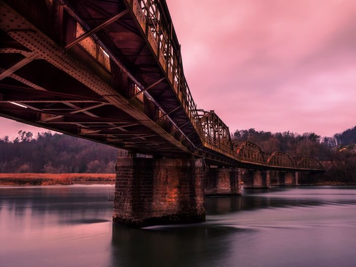 Low angle view of bridge over river at sunset