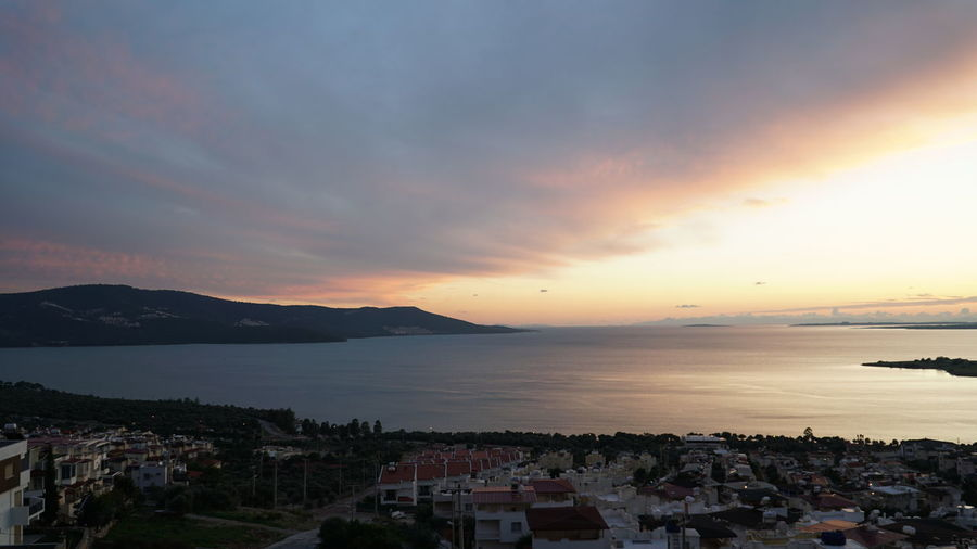 Scenic view of sea by town against sky during sunset