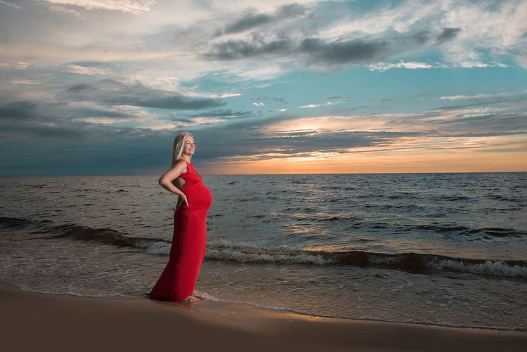 Side view of pregnant woman standing at beach against cloudy sky during sunset