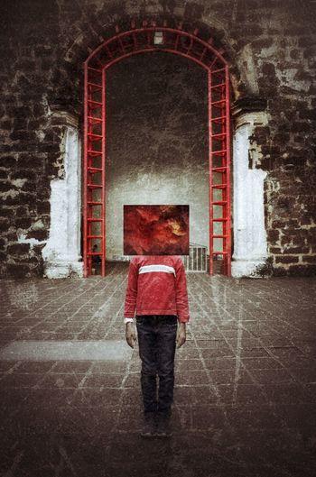 Rear view of man standing against red door