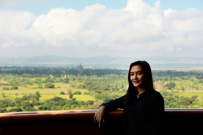 Portrait of beautiful young woman with landscape in background