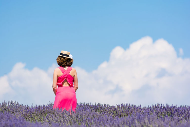 Woman in pink dress with hat standing in lavender field against sky during sunny day