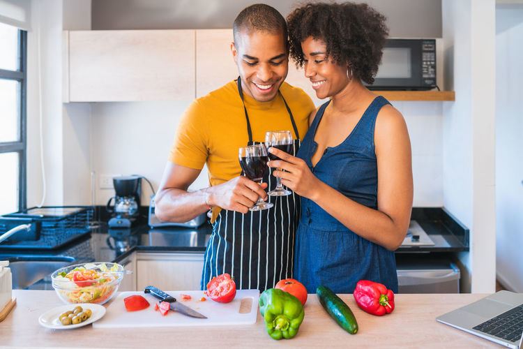 Smiling couple toasting drink while standing in kitchen