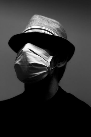 Close-up of man wearing hat and mask against gray background