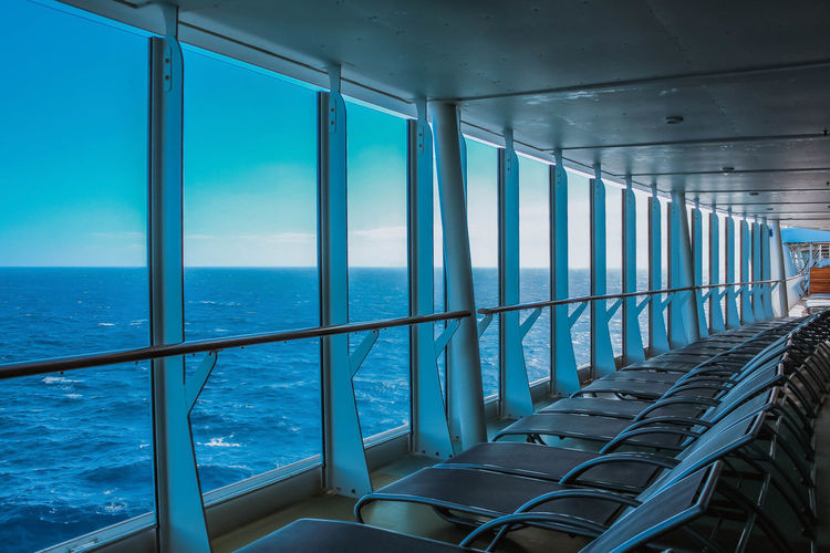 View outside the window on a ship Water Sea Architecture Glass - Material Indoors  No People Day Transparent Built Structure Railing Nature Blue Horizon Over Water Sky Window Transportation Sunlight Horizon Ceiling Cruise Cruise Ship Ship Boat Chairs Ocean Ocean View