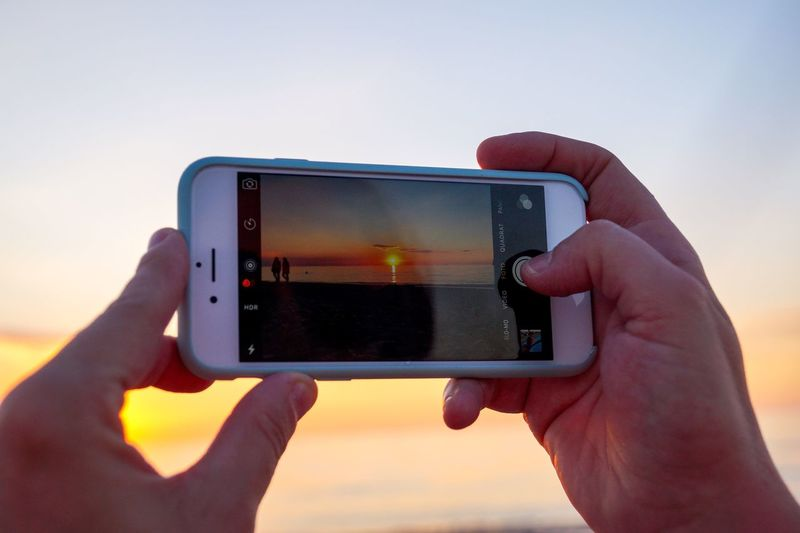 Sunset shoot.   Sunset Idyllic Germany Warnemünde Beach Silhouette Sun Summer Photographing Mobile Phone Smart Phone Photography Themes Holding Technology Portable Information Device Using Phone Water IPhone Leisure Activity Person Sony SLT-A58 Selective Focus Baltic Sea Seascape Horizon Over Water