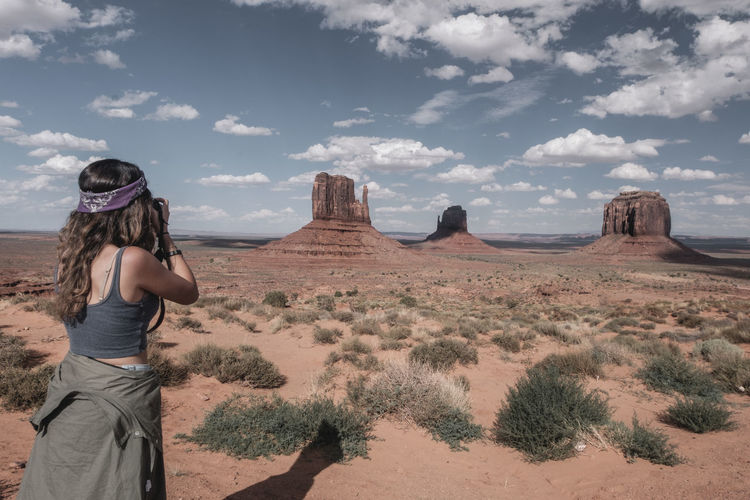Panoramic view of woman on desert against sky. shooting