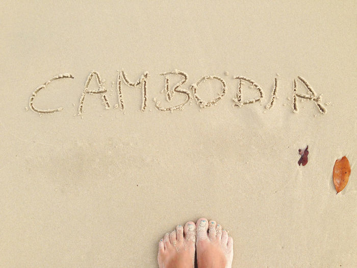 Low Section Of Woman Standing By Cambodia Text At Beach