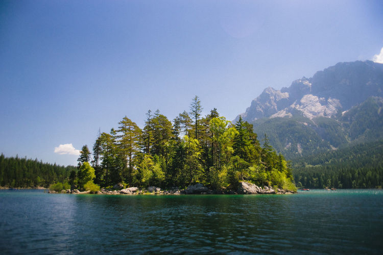 Lake and trees with mountain against sky