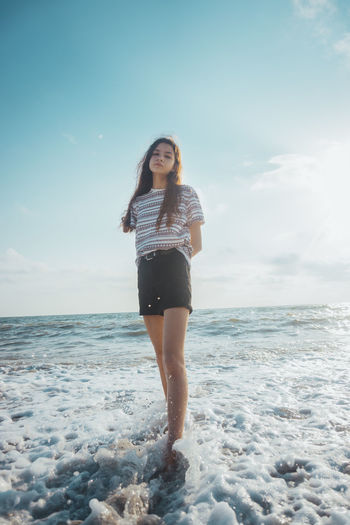 Portrait of young woman standing in sea against sky during sunny day