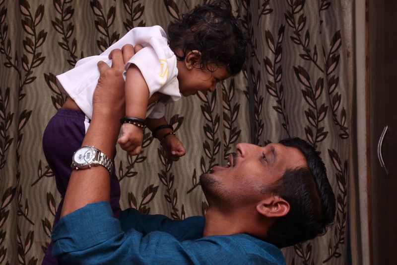 Side View Of Father Playing With Son At Home