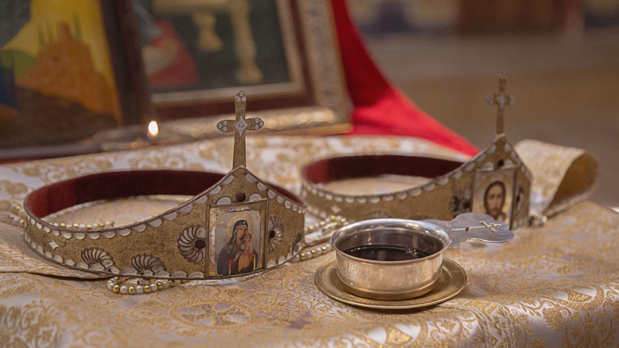 Close-Up Of Wine In Bowl By Crowns On Altar In Church