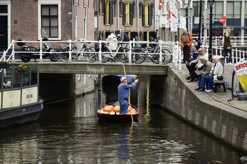 People standing on boat in canal