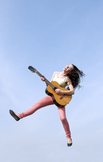 woman jumping with guitar Caper Fun Happy Jump Laughing Music Woman Clear Sky Ecstasy Enthusiastic Flying Full Length Guitar Happiness Hovering Instrument Joy Joyful Leap Jumping Lifestyles Musician Outdoors Playing Skip Young Women