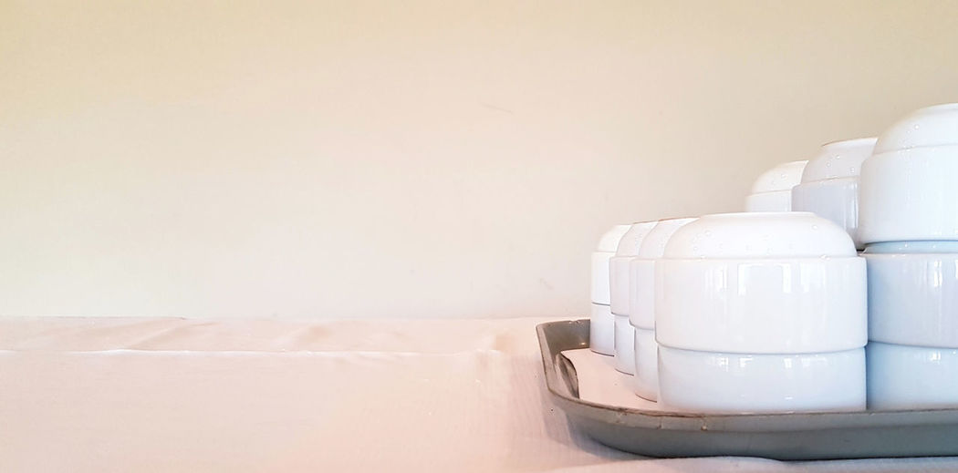 Close-up of white stack on table against wall at home