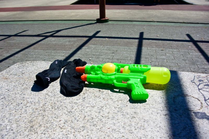 Spray pistol and socks at Fiesta del Agua in Vilagarcia de Arousa Fiesta Del Agua Lost Water Pistol Abandoned After Close-up Found Green Color No People Plastic Shadow Socks Street Supersoaker Water Water Gun Wet Rethink Things