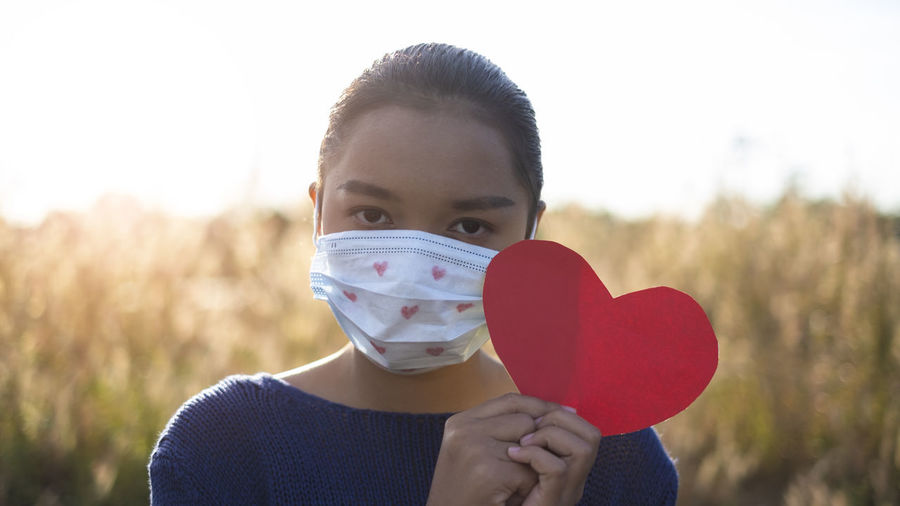 Portrait of girl wearing mask holding heart shape while standing outdoors
