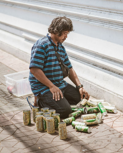 street seller making his products from empty beer cans Creative Creativity Small Business Street Seller Street White Wall Kneeling Cans Beers Thailand Lifestyles Container Day Real People One Person Men Food And Drink Striped Stripes Casual Clothing Shoulder Bag Pavement Long Hair Poverty Social Issues