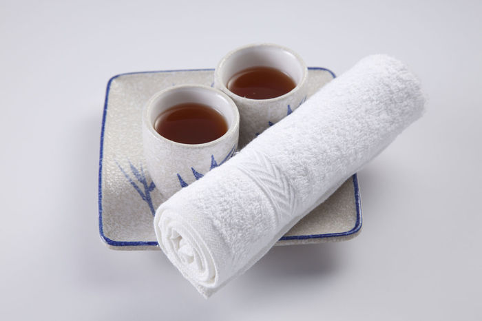 two cups of tea with rolled up towel Asian  Beverage Paint Rolled Up Served Service Tea Bamboo Close-up Day Hot Towel Japanese Drink No People Oriental Plate Ready To Serve Spa Studio Shot Tea - Hot Drink Traditional White Background