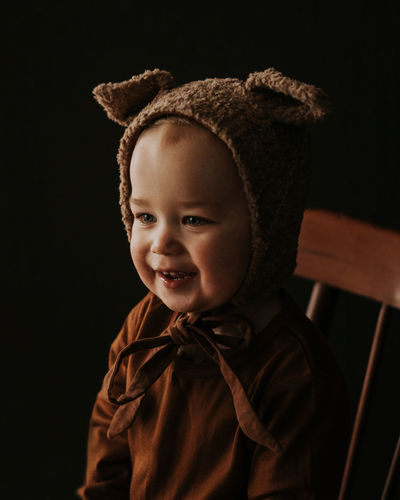 Toddler baby boy in funny costume with ears sitting and laughing