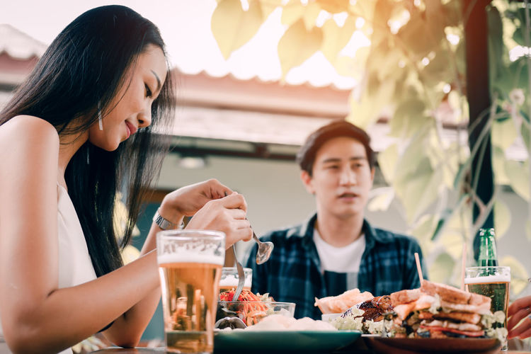 Midsection of woman sitting at restaurant table
