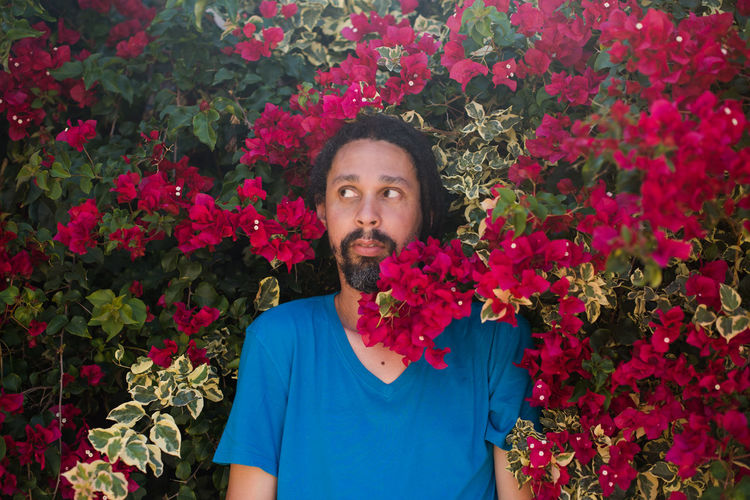 Thoughtful man standing amidst bougainvillea