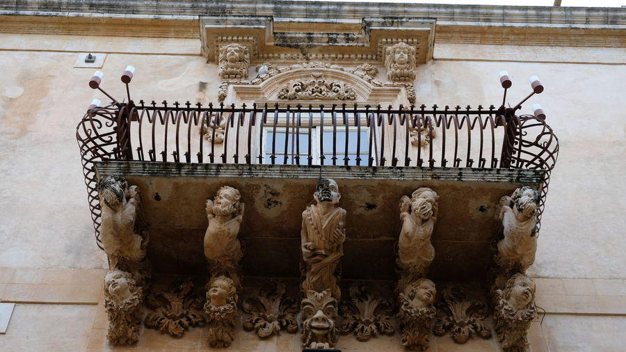 City of Noto. Province of Syracuse, Sicily. One of the spectacular balconies of the Palazzo Nicolaci. The entire city of Noto is known as one of the most remarcable examples of the sicilian baroque style. Noto,sicily Syracuse  Sicilian Baroque Architecture Antiques Details Close-up Elaborate Architectural Detail Balcony Rare Peculiar Architecture Palazzo Nicolaci Sandstone Child Old Man Iron Work Craftsmanship  Ornate Building Exterior Sculpture
