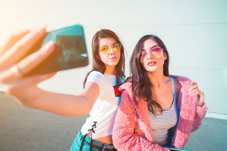 Young woman taking selfie from mobile phone with friend