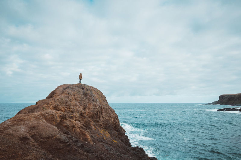 Rear View Of Woman Standing On Cliff By Sea Against Cloudy Sky