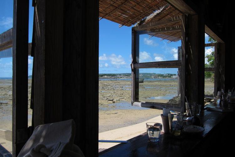 Beach against sky seen through home window