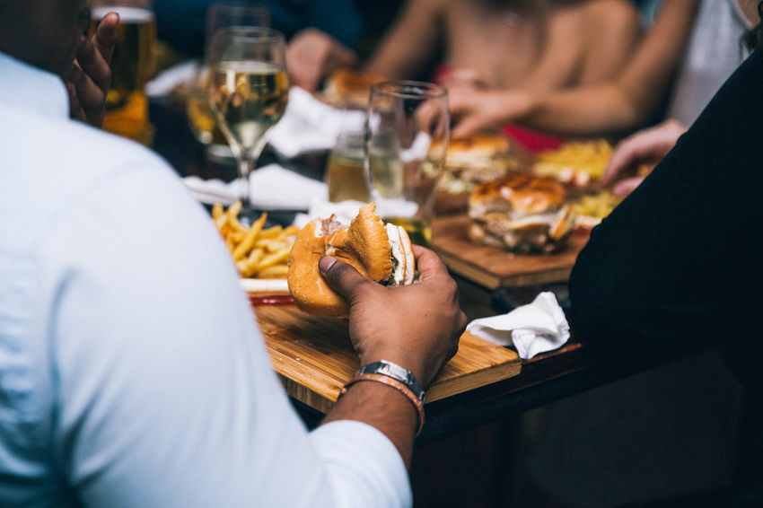 Adult Business Celebration Food Food And Drink Freshness Glass Group Of People Hamburger Hand Holding Human Hand Indoors  Lifestyles Men Midsection People Real People Restaurant Selective Focus Table Women
