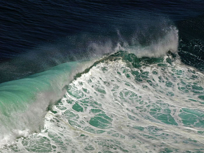 Close up of wave splashing and curling in sea
