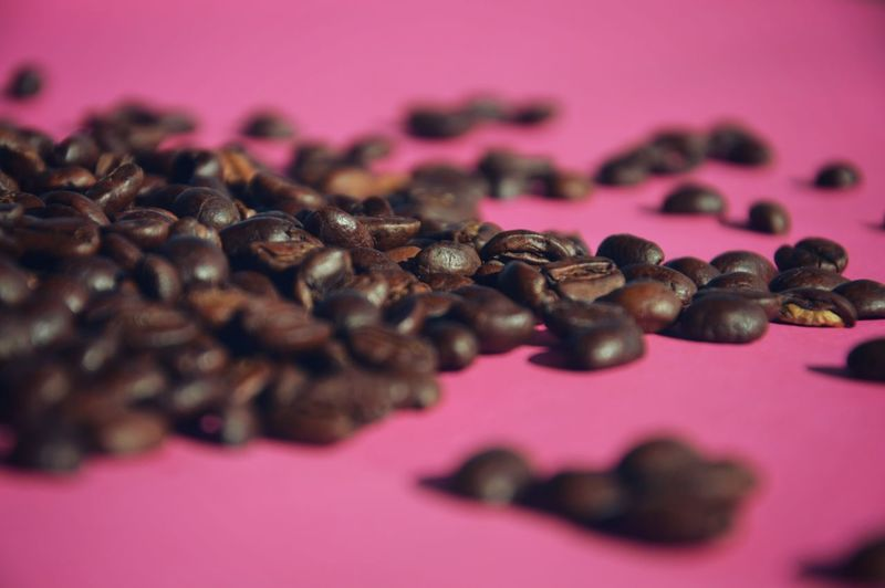 Close-up of roasted coffee beans on pink table