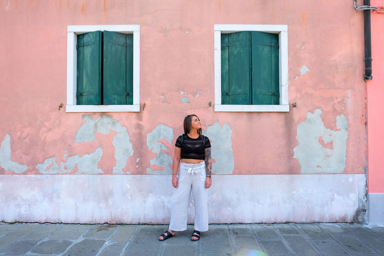 woman looking away from the camera on pink wall Young Adult Italy Venice Venice, Italy Pink Color Pink Woman Women colour of life Pop Of Color Burano Burano, Italy One Person Full Length Architecture Building Exterior Standing Real People Front View Day Built Structure City Entrance Looking At Camera Building Portrait Adult Casual Clothing Door Outdoors Beautiful Woman Hairstyle Model Looking Away