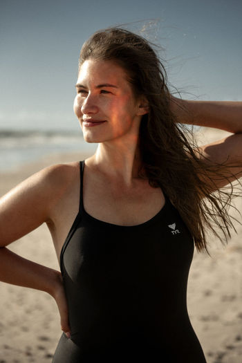 Beautiful woman standing at beach against sky
