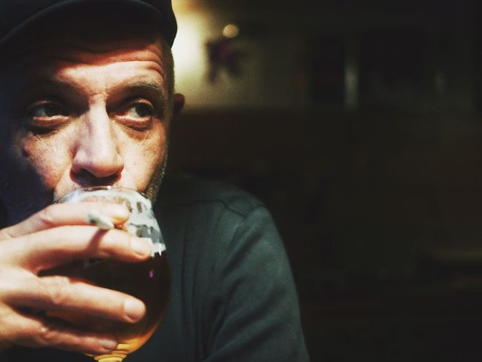 Close-Up Of Man Drinking Beer While Holding Cigarette At Home