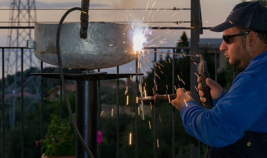 Mid Adult Man Welding Metal By Railing During Sunset