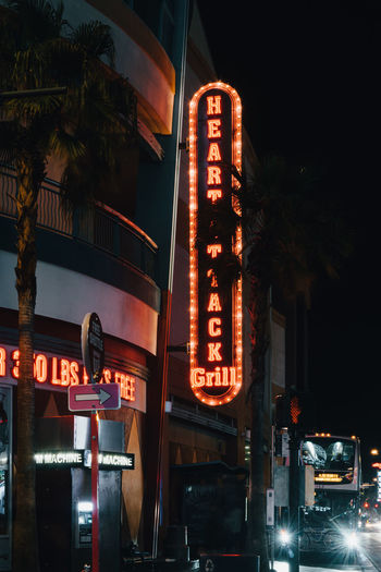 Low angle view of illuminated sign in city at night