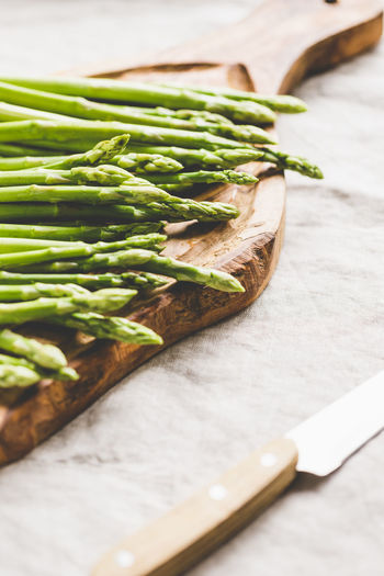 Food And Drink Food Healthy Eating Freshness Still Life Wellbeing Vegetable Green Color Table Indoors  No People Wood - Material Close-up Selective Focus Raw Food High Angle View Asparagus Kitchen Knife Focus On Foreground Cutting Board Vegetarian Food