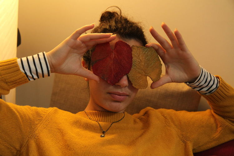 Young woman covering eyes with leaf decorations at home