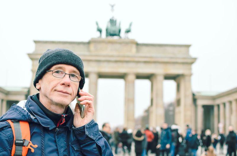 Portrait of man talking on phone against brandenburg gate