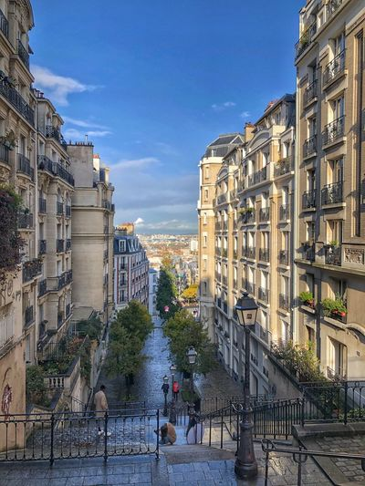 Buildings by street in city against sky