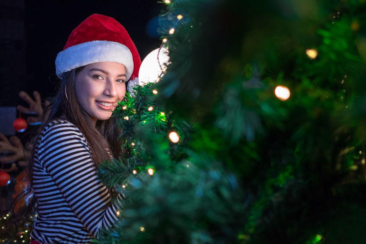 Portrait of smiling woman by illuminated christmas tree at night