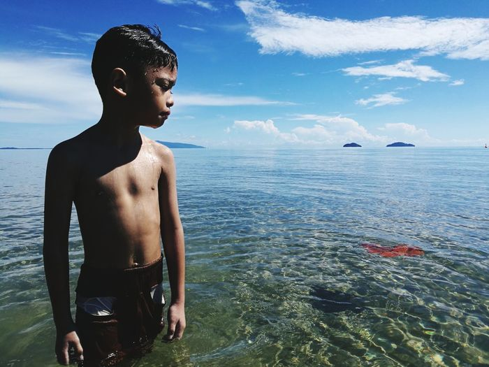 Shirtless boy standing in sea against sky