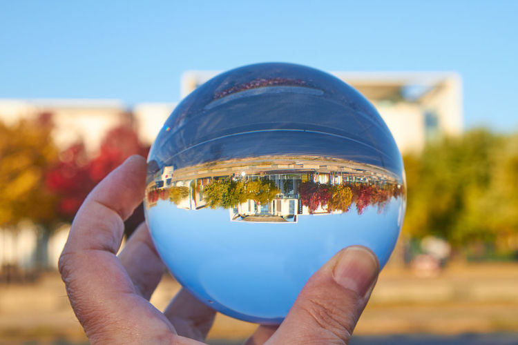 Close-up of hand holding crystal ball against sky
